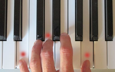 picture of hand playing a chord on piano